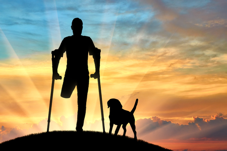 Silhouette of a man with an amputated leg standing with crutches at sunset with his dog. The concept of people with disabilities
