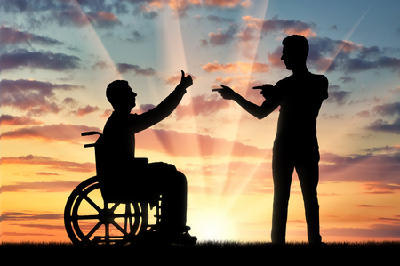 Happy disabled person in a wheelchair at sunset and comrade who supports it. The concept of persons with disabilities in society