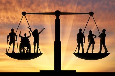 Inválidos iguais em direitos na balança com pessoas saudáveis. O conceito de igualdade social b legal das pessoas com deficiência na sociedade Foto de archivo