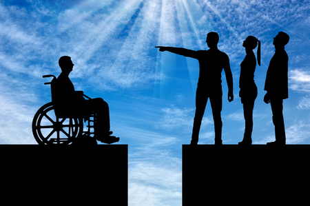 Crowd of people makes it clear to the disabled person in the wheelchair that he must walk away and the gap between them. The concept of Discrimination of people with disabilities in society Stock Photo