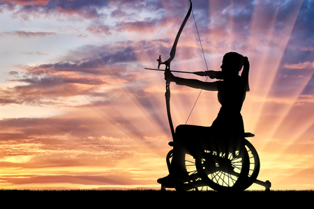 Silhouette of a disabled woman in a wheelchair engaged in sports archery. The concept of disabled people leading an active lifestyle
