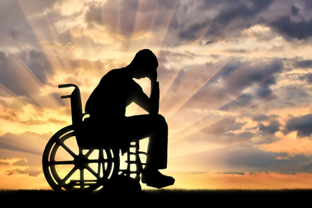 Silhouette of sad sad man in wheelchair in depression. The concept of people with disabilities experiencing dipression
