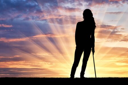 Silhouette of a disabled woman supports herself with a crutch admiring the sunset. The concept of people disabled with crutch Stock Photo