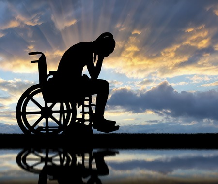 Silhouette of a sad disabled woman in a wheelchair by the river with her reflection. The concept of people with disabilities experiencing grief and sadness