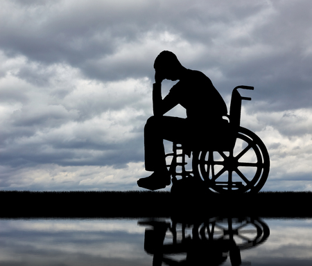 Silhouette of sad man crying in the disabled wheelchair. The concept of people with disabilities experiencing grief for the loss of health