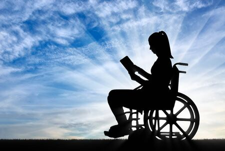 Silhouette of a disabled woman in a wheelchair reading a book in the fresh air. Concept of the way of life of people with disabilities