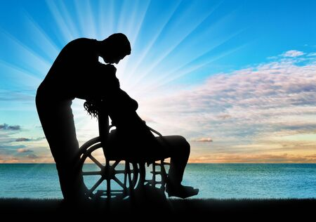 Silhouette of a man kissing a disabled woman in a wheelchair by the sea. The concept of a person with a disability in the family