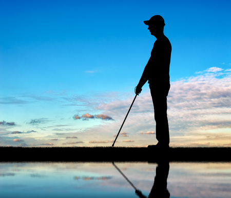 Silhouette of a blind man with a cane in his hand, stands by the river with his reflection. The concept of blind people with disabilities