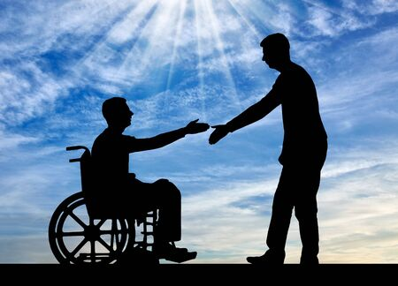 The employer intends to shake hands with a man in a wheelchair. The concept of providing work to people with disabilities Stock Photo