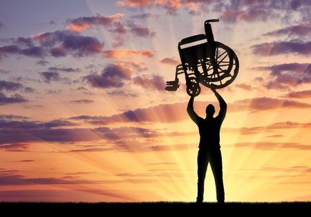 Silhouette of a disabled man standing while lifting a wheelchair against the sunset background. The concept of people defeating disease