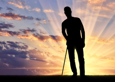 Silhouette of a disabled man supports himself with a crutch against the sunset background. Concept of people in rehabilitation Stock Photo