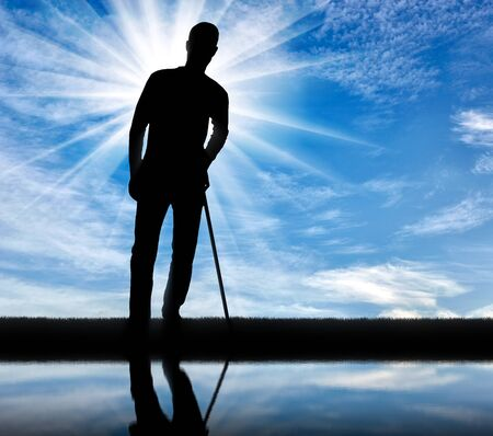 Silhouette of a disabled man supports himself with a crutch near the river with his reflection. Concept of people with disabilities