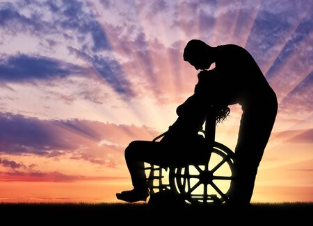 Silhouette of a man kissing a disabled woman in a wheelchair at sunset Stock Photo