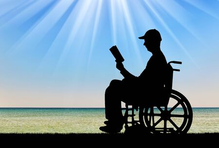 Silhouette of a disabled man in a wheelchair reading a book by the sea. Concept of the way of life of people with disabilities Stock Photo