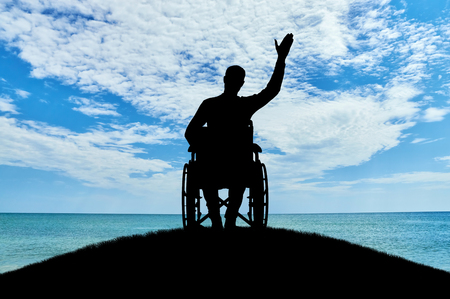 Silhouette of a disabled man in a wheelchair friendly waving his hand atop a hill near the sea. The concept of people with disabilities 写真素材
