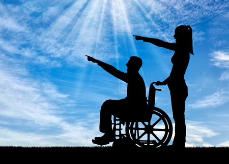 Silhouette of a disabled man in a wheelchair and his wife have a good time. The concept of caring and supporting disabled people in the family