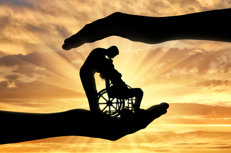 Silhouettes of a happy disabled woman in a wheelchair with a man who kisses her. The concept of support and assistance for people with disabilities