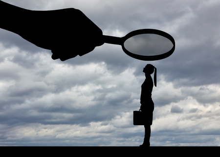 Silhouette of an employee woman. A hand with a magnifier over a woman.