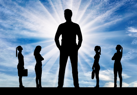 Silhouette of a big man and four small women near him. The concept of gender inequality and discrimination against women Stock Photo