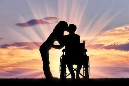 Silhouette of a disabled man in a wheelchair and his wife who is kissing. The concept of caring and supporting disabled people