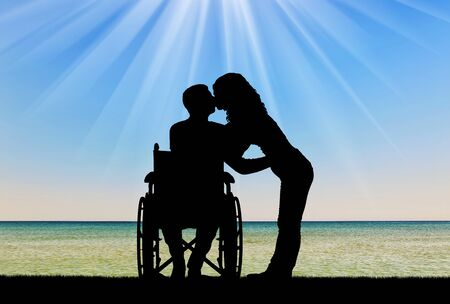 Silhouette of a disabled man in a wheelchair and his wife who is kissing by the sea. The concept of caring and supporting disabled people Stock Photo