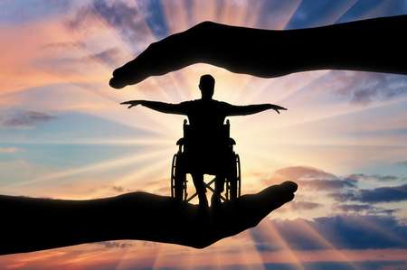 Silhouette of happy disabled man in wheelchair in hands of help. The concept of protection and help to people with disabilities
