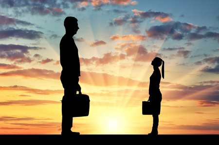 Silhouette of workers, a big man and a small woman. The concept of gender inequality in a career
