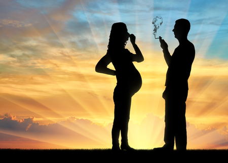 Silhouette of a man egoist smoking near a pregnant woman as she covers her nose with her hand from the smoke.