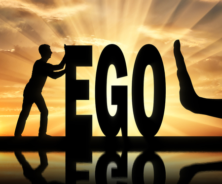Gesture of the hand stop and silhouette of the man pushing the word ego. Stock Photo