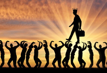 Silhouette of a walking man with a crown on his head on the hands of the crowd. Archivio Fotografico