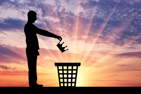 Silhouette of a man throws a crown in the garbage bin. Stock Photo