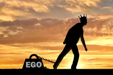 A big weight in the form of an ego is chained to the foot of a man with a crown on his head.