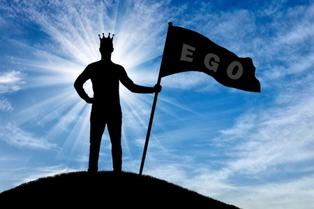 Silhouette of a selfish man with a crown on his head holds a flag with the word ego on top of a hill. The concept of selfishness and narcissism