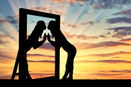 Woman is kissing her reflection in the mirror. The concept of narcissism and selfishness Imagens