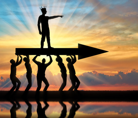 The silhouette of a selfish man with a crown on his head indicates to people who carry him, where to move. The concept of selfish behavior towards other people Stock Photo