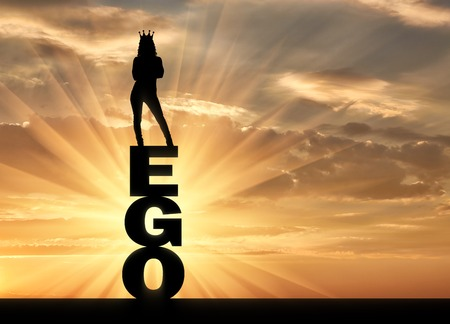 Silhouette of a narcissistic and selfish woman with a crown on her head standing on the word ego. The concept of narcissism and selfishness