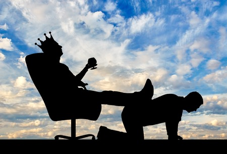 Silhouette of a selfish man with a crown on his head sitting in an armchair, threw back his legs on the mans back. The concept of a businessman is an egoist who does not respect his employees