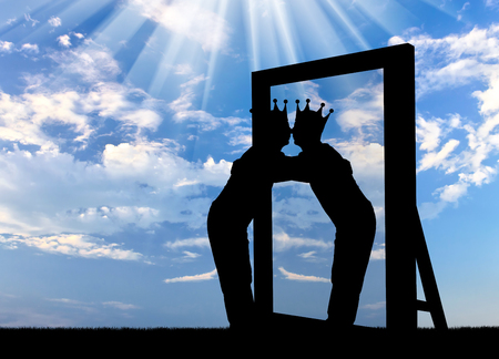 Silhouette of a narcissistic man with a crown on his head hugging his reflection in the mirror. The concept of narcissism and selfishness