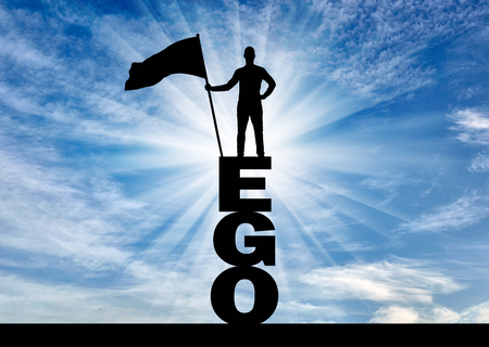 Silhouette of a selfish man who holds a flag on top of the word ego. The concept of selfishness and narcissism Reklamní fotografie