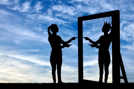 A silhouette of a narcissistic woman raises her self-esteem in front of a mirror. The concept of narcissism and selfishness Foto de archivo