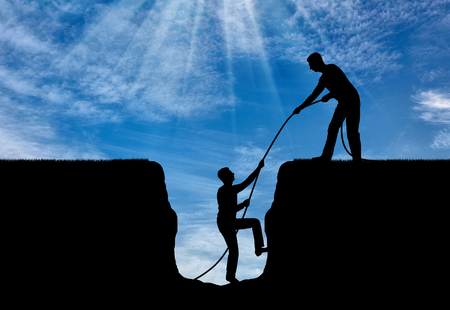 A silhouette of a man helps to get out of the pit to another. The concept of teamwork and mutual aid