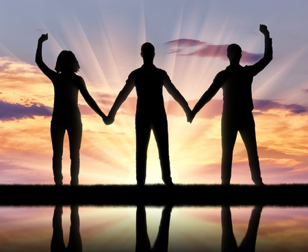 Silhouette of a group of happy people of three people holding hands. The concept of mutual assistance