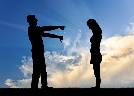 A silhouette of a man showing a finger at a woman telling her that she is a loser. The concept of social problems, humiliation of women Stock Photo