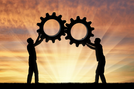 Silhouette of two men holding gears put them together in one gear. The concept of mutual funds