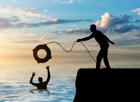 A silhouette of a man throws a lifeline to another man who is drowning in the water. The concept of mutual assistance in a business team Stock Photo