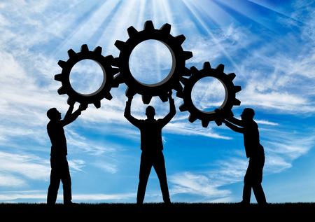 Silhouette of the three men holding the gears put them together in one gear. The concept of mutual benefit