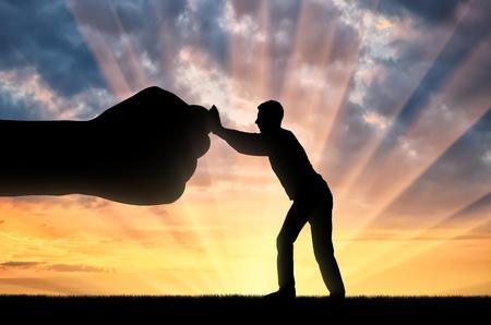 Silhouette of man resists big fist hand. The concept oppression 版權商用圖片