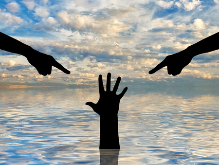 Silhouette of two hands showing a finger and condemning the hand of a sinking person asking for help. The concept of a selfish society, a social problem