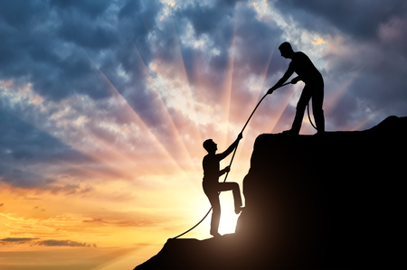 Silhouette climber helps to climb the top of another climber, throwing him a rope. Conceptual help scene Stock Photo