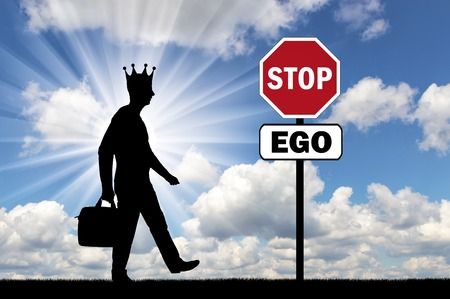 Silhouette of a selfish man with a crown on his head and a road sign of a stop ego. The conceptual scene of selfishness as a problem of society Stock Photo